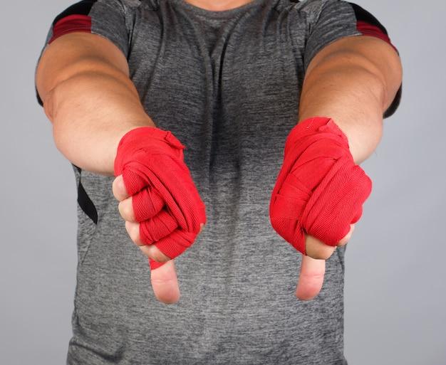 De volwassen atleet in grijs eenvormig en handen teruggewonden met textielverband toont afkeergebaar