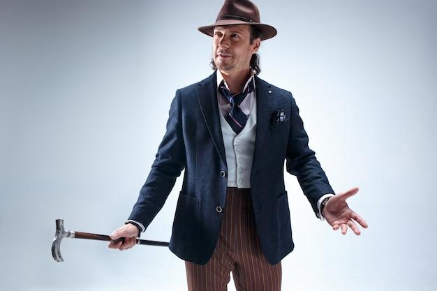 De volwassen bebaarde man in een pak en hoed met stok. geïsoleerd op een grijs.