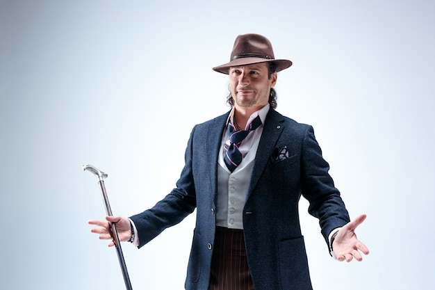 De volwassen bebaarde man in een pak en hoed met stok. geïsoleerd op een grijze studio.