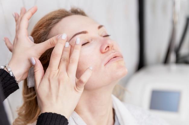 De volwassen blondevrouw past gezichtscrème in een schoonheidssalon toe. detailopname. leeftijdsgebonden schoonheidsbehandelingen.