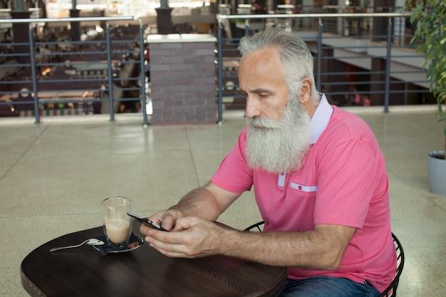 De volwassen gebaarde mens verbond op smartphone bij koffiewinkel