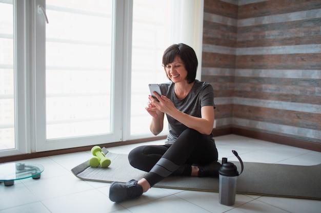 De volwassen geschikte slanke vrouw heeft thuis training. de vrouwelijke persoon zit op yogamat en gebruikt smatphone met handen. ontspan en rust pauze of pauze tijdens het sporten.