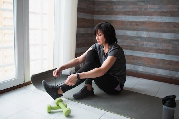 De volwassen geschikte slanke vrouw heeft thuis training. ernstig hardwerkend volwassen model zit op yogamat om veters te strikken. klaar voor het sporten.