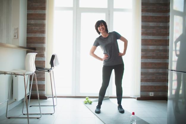 De volwassen geschikte slanke vrouw heeft thuis training. ernstige volwassen vrouwelijke persoon die alleen in de kamer. lichaam strekken en opwarmen. volwassen goedgebouwde prachtige vrouw in geweldige vorm.