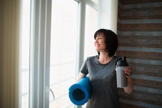 De volwassen geschikte slanke vrouw heeft thuis training. ga na de training staan met wat eiwitdrank en yogamat in handen. zorg voor slanke goede lichaamsvorm en welzijn.