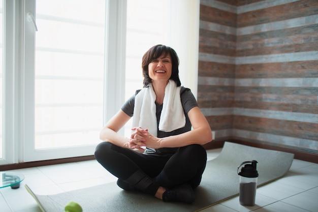De volwassen geschikte slanke vrouw heeft thuis training. ga op de yogamat zitten en houd de appel in handen. snacktijd na het sporten. zorg voor gezondheid en welzijn.