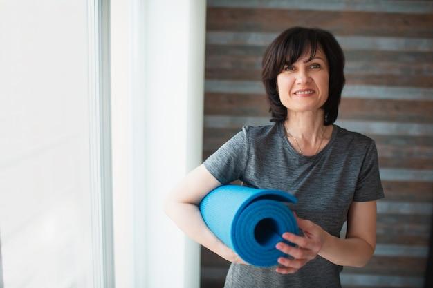 De volwassen geschikte slanke vrouw heeft thuis training. goed gebouwde senior volwassen vrouwelijke persoon houdt yogamat in handen en kijkt op de camera. zorg voor een mooi uiterlijk en gezondheid.