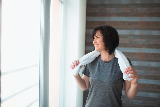 De volwassen geschikte slanke vrouw heeft thuis training. goed gebouwde sterke senior vrouwelijke persoon staat alleen in de kamer na het sporten. met witte handdoek om de nek. rust en ontspan.