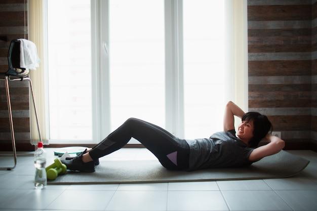 De volwassen geschikte slanke vrouw heeft thuis training. goed gevormde senior vrouw doet abs oefening. zorg ervoor dat het lichaam jong en gezond blijft.