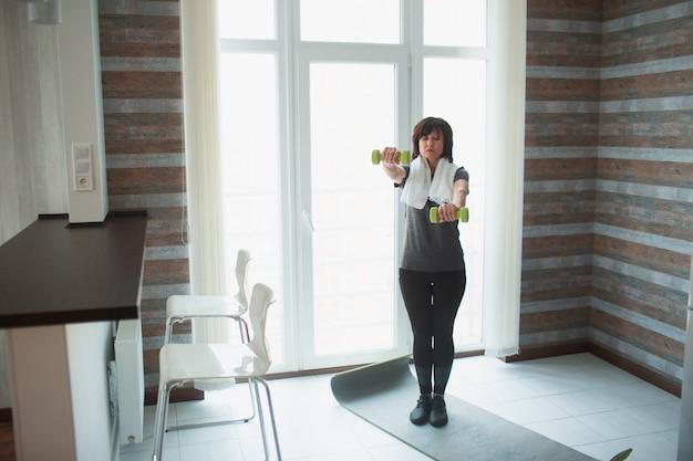 De volwassen geschikte slanke vrouw heeft thuis training. het houden van halters met gestrekte handen en oefenen. senior vrouwelijke persoon zorgen over lichaam en gezondheid.