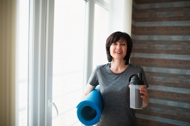 De volwassen geschikte slanke vrouw heeft thuis training. positieve vrolijke senior vrouwelijke persoon houd fles en yoga mat in handen. na de training voor een goede, gezonde lichaamsvorm. alleen in de kamer.