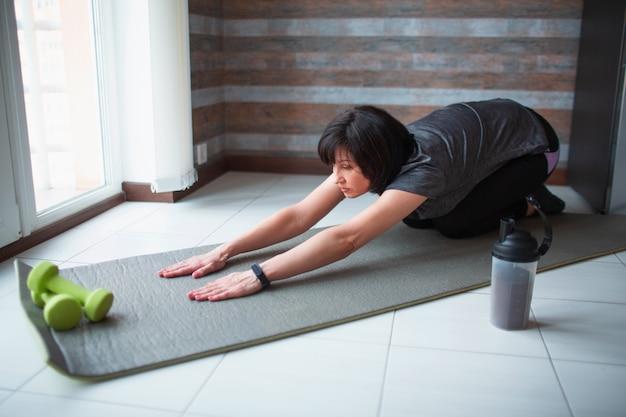 De volwassen geschikte slanke vrouw heeft thuis training. senior model zitten in asana pose en haar lichaam uitrekken. sterke rijpe vrouw die haar lichaam uitrekt.