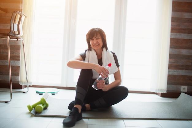 De volwassen geschikte slanke vrouw heeft thuis training. senior vrolijk aantrekkelijk model glimlachend op camera. zittend op yogamat en houd waterfles. pauze tijdens het sporten.