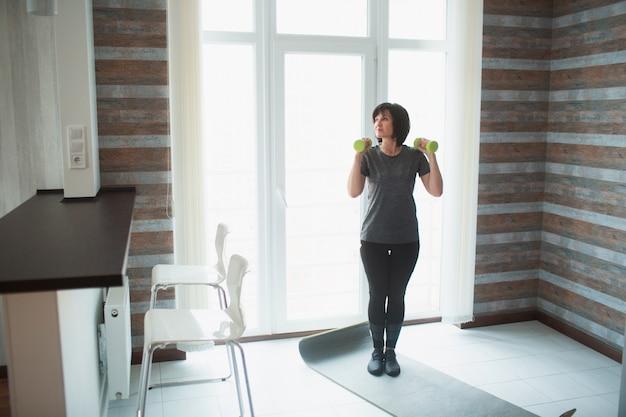De volwassen geschikte slanke vrouw heeft thuis training. senior vrouwelijke persoon staan met halters omhoog en klaar om te oefenen. alleen in de kamer. slim fit vrouw zorgen over gezondheid.