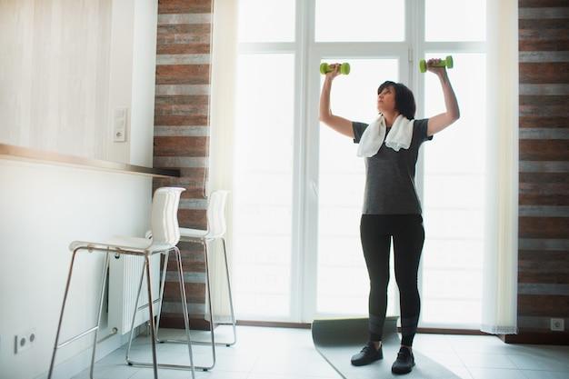 De volwassen geschikte slanke vrouw heeft thuis training. sta alleen in de keuken en oefen met halters. houd ze in de lucht. senior slanke goedgebouwde vrouw die slank en in goede vorm wordt.