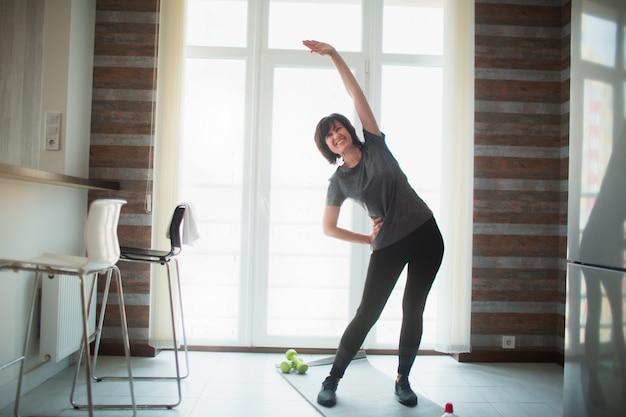 De volwassen geschikte slanke vrouw heeft thuis training. trainen zonder apparatuur en haar lichaam strekken. senior goed gebouwde vrouw zorgen over gezondheid en lichaamsvorm.