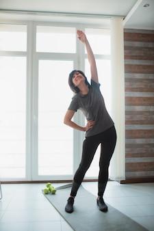 De volwassen geschikte slanke vrouw heeft thuis training. verticaal beeld van goed gebouwde in goede vorm vrouwelijke persoon die haar lichaam oprekt. trainen zonder apparatuur in de kamer.