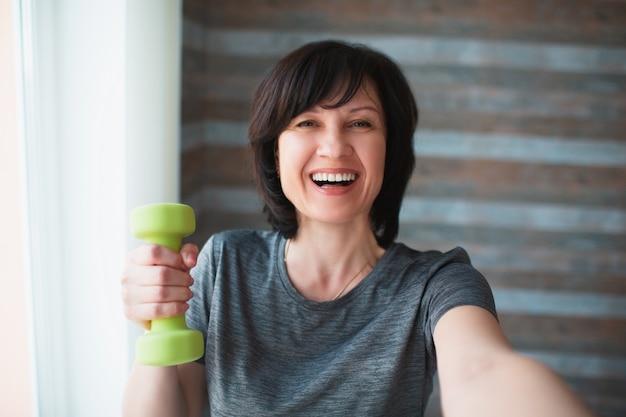 De volwassen geschikte slanke vrouw heeft thuis training. vrolijke positieve gelukkig volwassen senior vrouwelijke persoon glimlach. goed gebouwde prachtige vrouw houdt een groene halter in de hand en poseren op camera. selfie tijd.