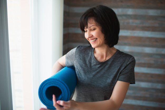 De volwassen geschikte slanke vrouw heeft thuis training. vrolijke positieve senior vrouwelijke persoon yoga mat in de hand houden en erop wijzen. glimlachend tijdens het staan in de kamer voor de training.