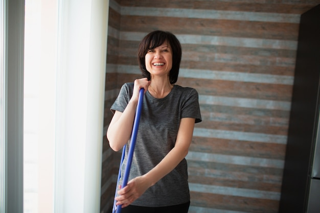 De volwassen geschikte slanke vrouw heeft thuis training. vrolijke positieve volwassen houden hoelahoep in de hand en glimlach. rusten na het sporten. zorgen voor wellness en mooie vorm.