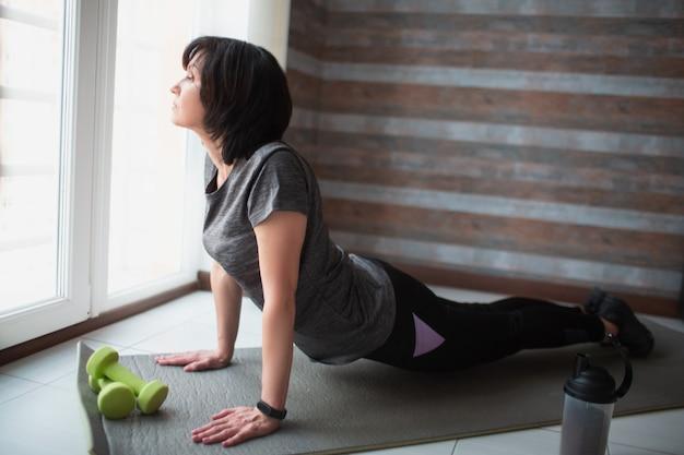 De volwassen geschikte slanke vrouw heeft thuis training. zijaanzicht die van hoger model zich op knieën bevinden en lichaam op mat houden. haar lichaam uitrekken en trainen.