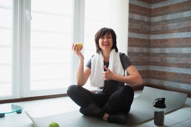 De volwassen geschikte slanke vrouw heeft thuis training. zit alleen op yogamat met appel in de hand. gezonde snack na het sporten. goed gebouwde sterke vrouw op foto.