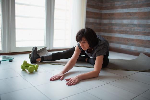 De volwassen geschikte slanke vrouw heeft thuis training. zittend op yogamat en strek lichaam naar voren. handen naar de vloer reiken. wellness en lichaamskracht.