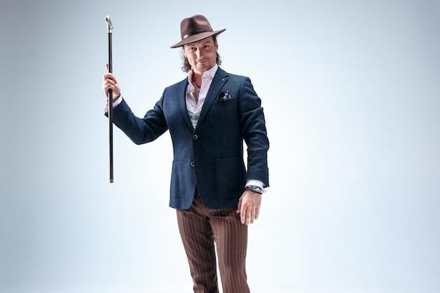 De volwassen man in een pak en hoed met stok.