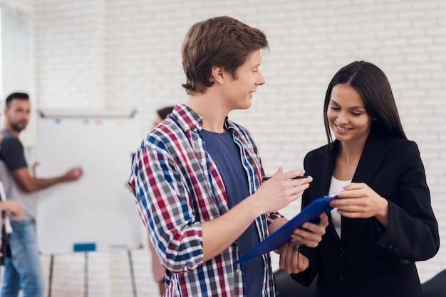 De volwassen man interviewt vrouw tijdens vergadering.