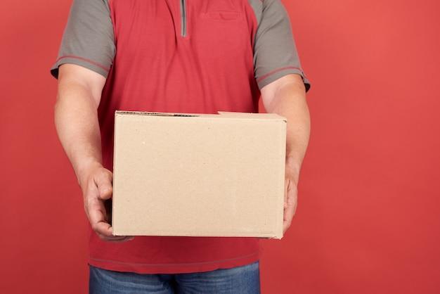 De volwassen mens in een rode t-shirt houdt een kartonnen bruine doos op een rode achtergrond, concept levering van goederen