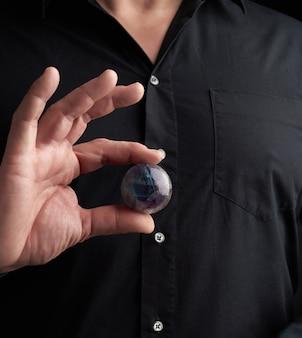 De volwassen mens in zwarte kleren houdt in zijn handen een glazen magische bal, voorwerp voor religieuze rituelen