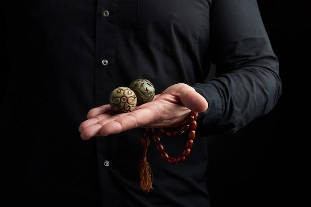De volwassen mens in zwarte kleren houdt in zijn handen een magische bal