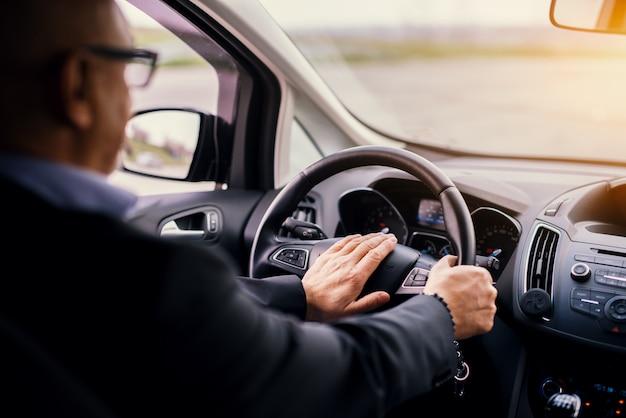 De volwassen professionele elegante zakenman in een kostuum drijft een auto en toetert.