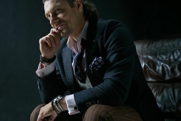 De volwassen stijlvolle man in een pak op een grijs. zakenmanzitting op een leunstoel