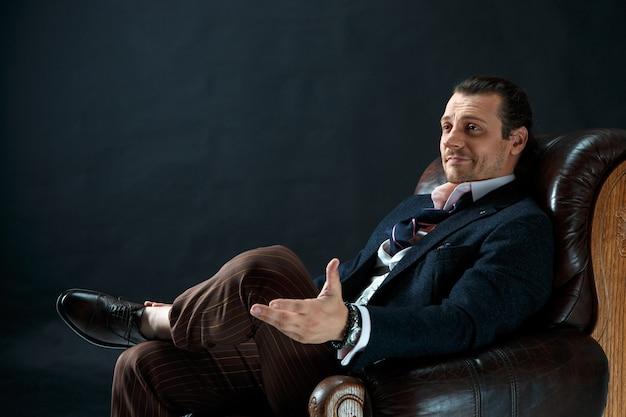 De volwassen stijlvolle man in een pak op een grijze studio. zakenmanzitting op een leunstoel