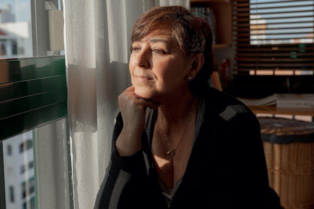 De volwassen vrouw die met kort haar wegkijken besteedt ontspannende tijd in haar studio terwijl het zonnebaden, thuis in quarantaine blijven.