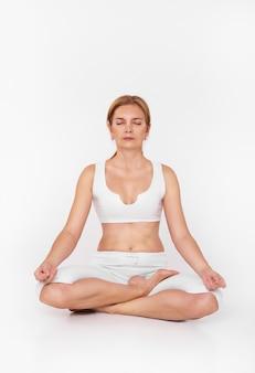 De volwassen vrouw die yoga doet, de vrouwenzitting in meditatieyoga stelt