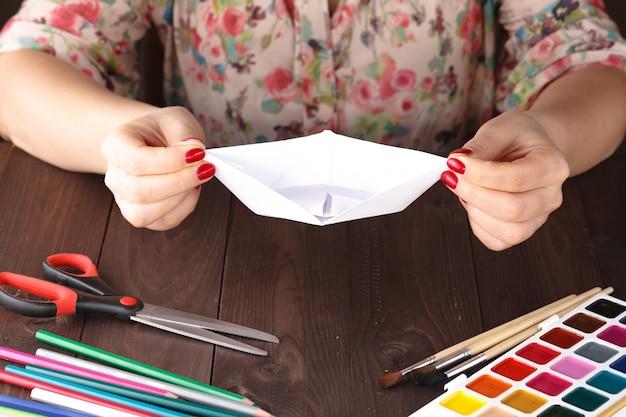 De volwassen vrouw doet origamiboot