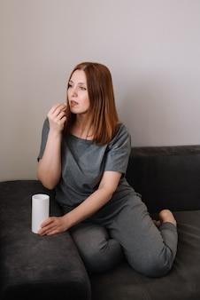 De volwassen vrouw neemt een zitting van de vitaminepil thuis op een laag in de woonkamer