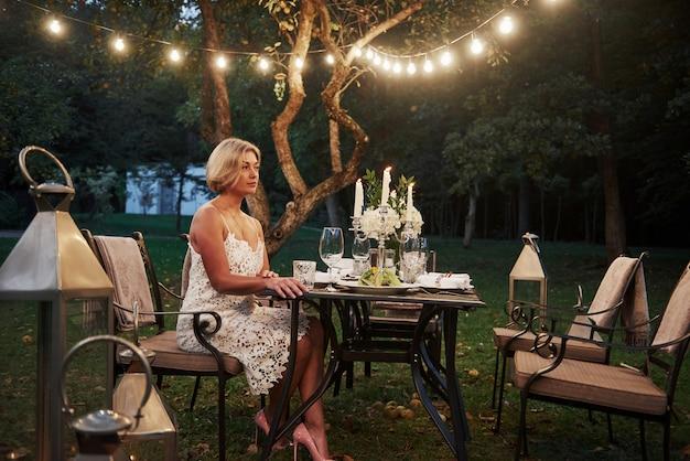 De volwassen vrouw zit op de stoel met kaarsen en wijnglazen in het openluchtdeel van restaurant
