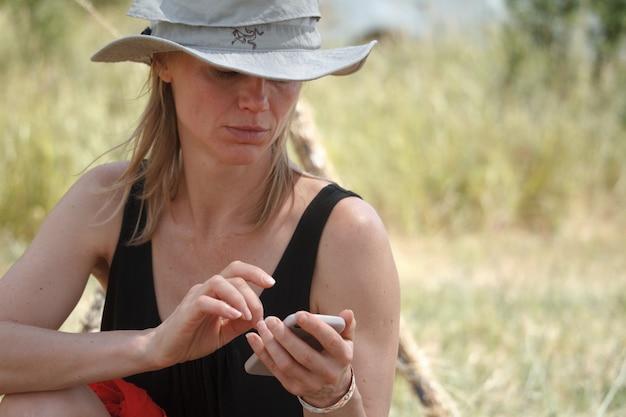 De volwassen vrouwenreiziger in een grijze hoed zit op de aard en gebruikt haar mobiele telefoon