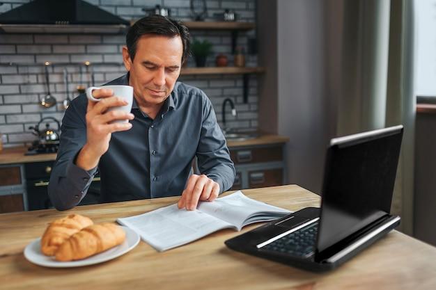 De volwassen zakenman zit bij lijst in keuken anr gelezen dagboek. hij houdt een witte beker vast en kijkt naar beneden. laptop en plaat met croissans op tafel.
