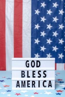 De vooraanzichtgod zegent het teken van amerika met vlaggen