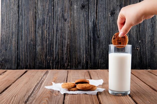 De vooraanzichtvrouw dunks havermeelkoekjes op calqueerdocument met glas melk op een houten achtergrond