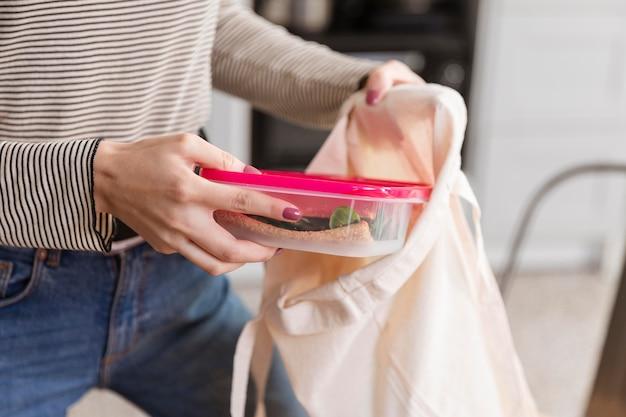 De vooraanzichtvrouw zet lunchdozen in zak