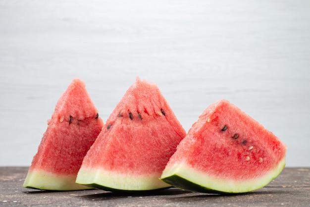 De vooraanzichtwatermeloen snijdt verse sappige en zachte vruchten op het sap van de grijze, fruitzomer