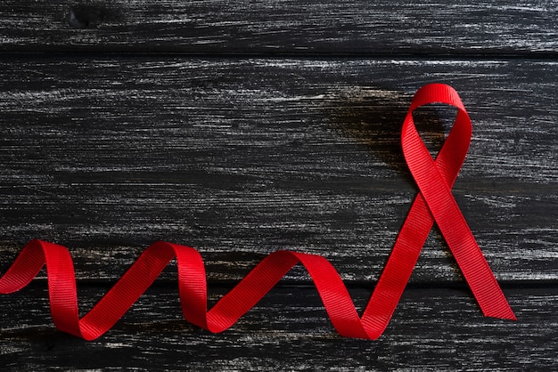 De voorlichting van het close-up rode lint op zwarte houten lijstachtergrond voor de campagne van de dag van de hulp van de wereld