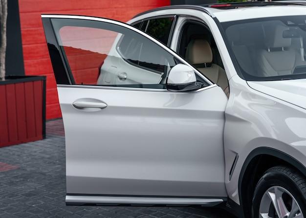 De voorste passagiersdeur is van dichtbij open. witte kleur moderne suv auto.