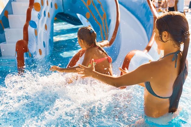 De voorzichtige oudere zus betrapt haar schattige kleintje die van de glijbaan recht in het zwembad glijdt en spettert