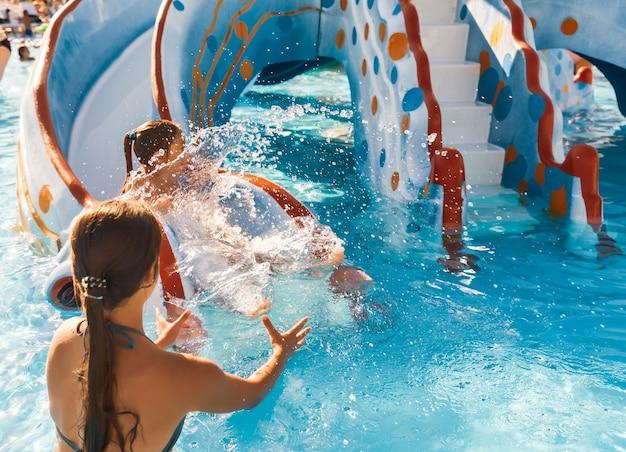 De voorzichtige oudere zus vangt haar schattige kleintje dat van de glijbaan in het zwembad glijdt en spettert